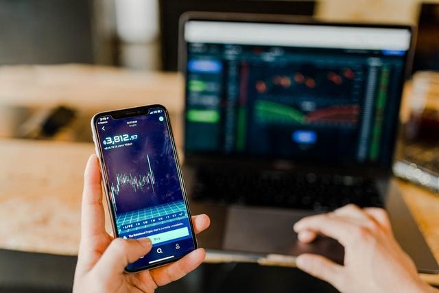 Telefon i komputer z notowaniami inwestycji